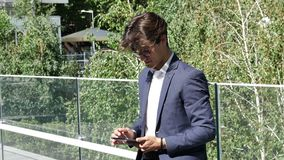Young business man using tablet PC outdoor. Handsome eleganty young business man wearing jacket standing, taking photo with tablet computer and then sending it stock video footage