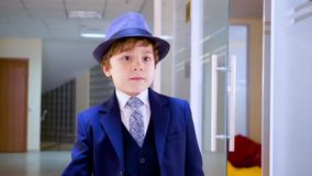 Young business man walking on corridor in business office. Serious young boy in business suit and hat walking on school stock footage