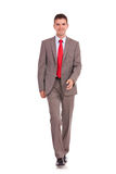 Young business man walking forward. A young business man is walking. He is smiling and looking to the camera. isolated over white background Royalty Free Stock Photos
