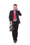 Young business man walking forward. While talking on the phone and holding a briefcase Stock Photo