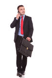 Young business man walking while holding a briefcase Royalty Free Stock Image