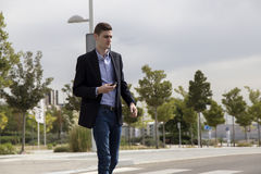 Young business man walking towards car, holding key. In his hand Royalty Free Stock Images