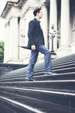Young business man on way to work climbing steps Stock Photo