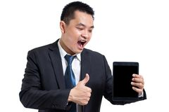 Young business man wear black suit working on digital tablet. Businessman hand holding tablet and hand thumbs up. royalty free stock image