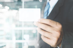 Young business man wear suit holding white business card Stock Photography