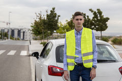 Young business man wearing reflective vest, outside car, Royalty Free Stock Photography