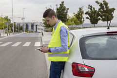 Young business man wearing reflective vest, outside car, Royalty Free Stock Photos