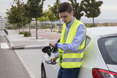 Young business man wearing reflective vest, outside car Royalty Free Stock Photography