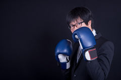 Young business man wearing suit with boxing gloves royalty free stock photos