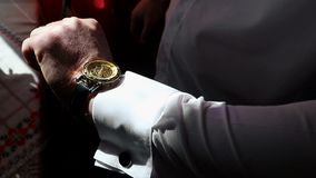 A young business man wears an expensive golden watch on his arm. Looking at the clock and hiding his hand.