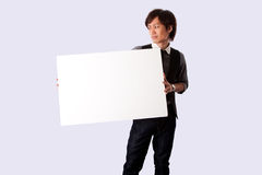 Young business man with white board. Young Asian business student man standing holding a white blank board and looking at it, isolated Stock Photography