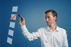 Young business man in white shirt checking on checklist box. Blue background. Stock Photography