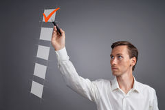 Young business man in white shirt checking on checklist box. Gray background. Stock Photos