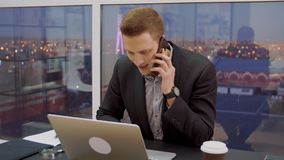 Young business man on window background while mobile conversation at work table. Satisfied business man on window background while mobile conversation at work stock video footage