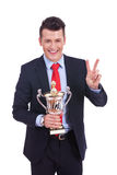 Young business man winning a big trophy Stock Photography