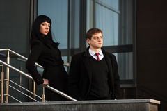 Young business man and woman against office buildi Stock Images