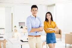 Young business man and woman standing in office Stock Image