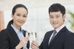 Young business man and woman toasting with champagne flutes Royalty Free Stock Image
