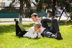 Young business man and woman using laptop in park Stock Images