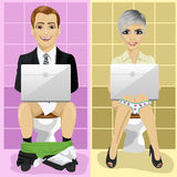 Young business man and woman using laptops on toilet Stock Image