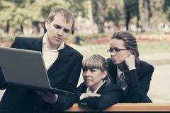 Young business people using laptop in city park royalty free stock image