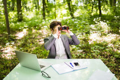 Young handsome business man at work table office with laptop in green forest with binocular looking for competitors. Business conc Royalty Free Stock Photo