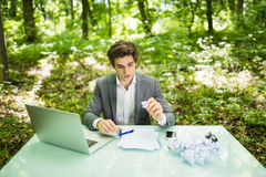 Young handsome business man at work table office with laptop in green forest with broke papers blank angry and sad no ideas. Busin Stock Photo