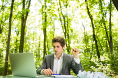 Young handsome business man at work table office with laptop in green forest with crumpled papers feeling exhausted. Business conc Stock Photography