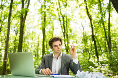 Young handsome business man at work table office with laptop in green forest with crumpled papers feeling exhausted. Business conc Royalty Free Stock Photo