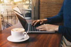 Young business man working at a coffee shop with a laptop royalty free stock photography