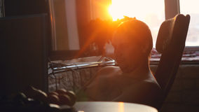 Young business man working on a computer at home through the sun, in view of the profile against the window during Stock Photo