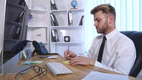 Young business man working on computer and making notes in notebook while sitting at the table in office stock video