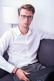 Young business man working at home on couch stock image