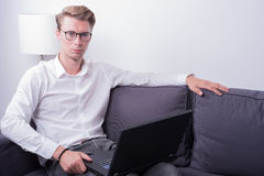 Young business man working at home on couch royalty free stock images