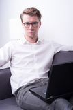 Young business man working at home on couch royalty free stock image