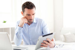 Young business man working at home on his tablet Stock Images