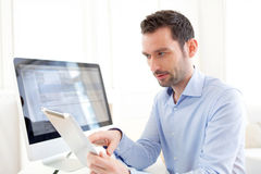 Young business man working at home on his tablet Royalty Free Stock Image