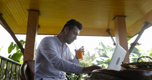 Young business man working on laptop during breakfast on summer terrace hotel in tropical forest, guy drink juice while stock video footage