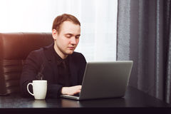 Young business man working on laptop. Hot coffee near Royalty Free Stock Photos