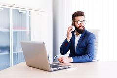 Young Banker Talking On Phone While Works On Laptop. Young Business Man Working On Laptop At Office - Workplace Royalty Free Stock Image