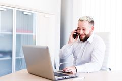 Young Banker Talking On Phone While Works On Laptop. Young Business Man Working On Laptop At Office - Workplace Royalty Free Stock Photo