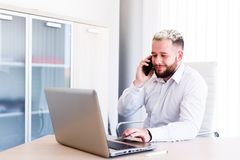 Young Lawyer Talking On Phone While Works On Laptop. Young Business Man Working On Laptop At Office - Workplace Royalty Free Stock Image