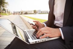 Young business man working on a laptop sitting on the street. Young business man working on a laptop sitting on the street Royalty Free Stock Photography