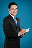 Young business man writing. Portrait of a handsome young business man with pen writing on binder clip Royalty Free Stock Image