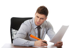 Young business man writing a note. Handsome businessman writing a note in the office Royalty Free Stock Image