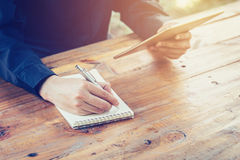Young business man writing note pad and using tablet in coffee s Royalty Free Stock Photography
