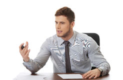 Young business man writing a note. Talking businessman writing a note in the office Royalty Free Stock Photos