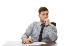 Young business man writing a note. Thoughtful businessman writing a note in the office Royalty Free Stock Photography