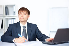 Young business man writing on paperwork in office Stock Images
