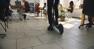 Young business manager riding kick scooter in modern trendy office. Futuristic multiethnic loft workplace atmosphere. Young business manager riding kick scooter stock footage